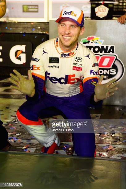 Denny Hamlin driver of the FedEx Express Toyota makes hands prints and foot prints in cemete in victry lane after winning the Monster Energy NASCAR...