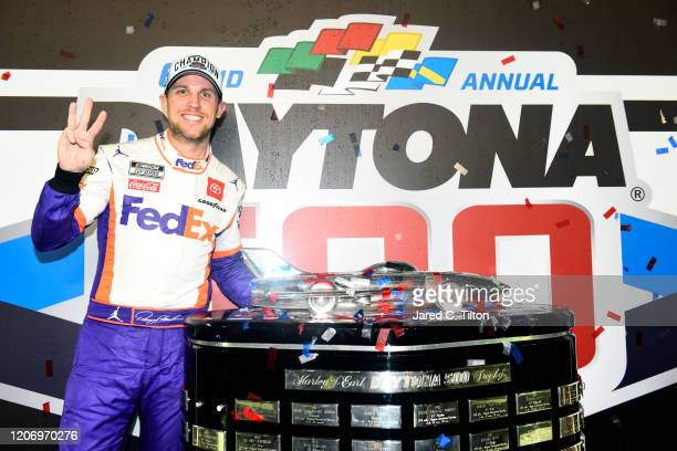 Denny Hamlin driver of the FedEx Express Toyota poses with the trophy in Victory Lane after winning the NASCAR Cup Series 62nd Annual Daytona 500 at...