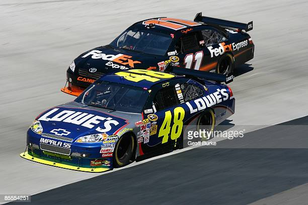 Denny Hamlin driver of the FedEx Express Toyota races Jimmie Johnson driver of the Lowe's Chevrolet side by side during the NASCAR Sprint Cup Series...
