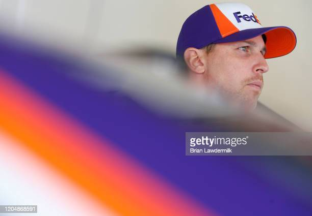 Denny Hamlin, driver of the FedEx Express Toyota, stands in the garage area during practice for the NASCAR Cup Series Busch Clash at Daytona...