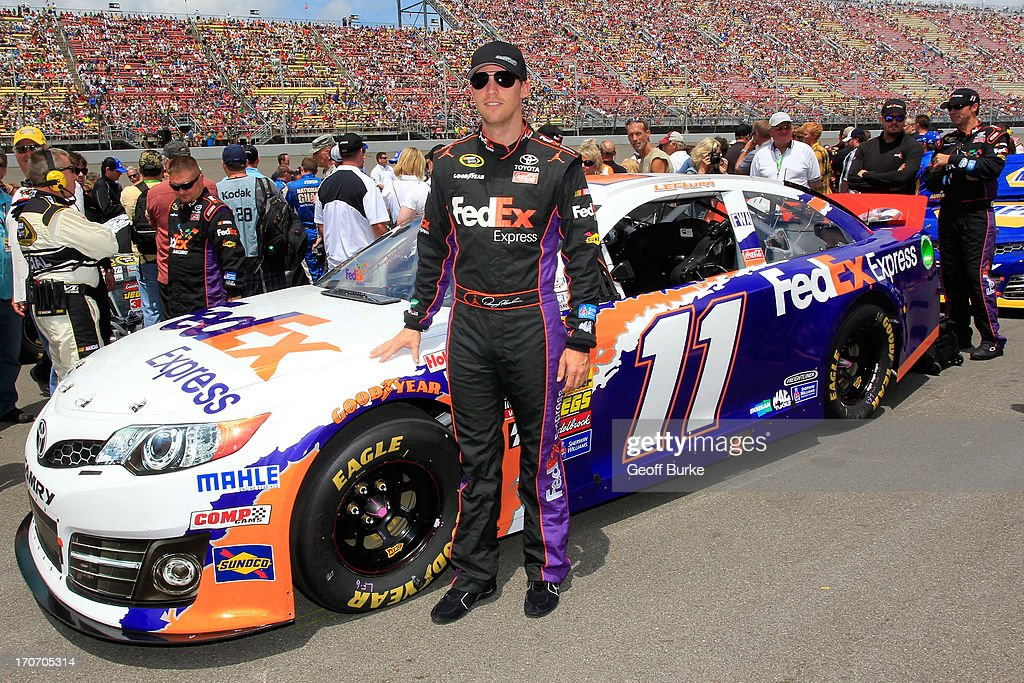 Denny Hamlin, driver of the #11 FedEx Express Toyota, stands on the grid by his car, which is carrying a special paint scheme honoring the late Jason Leffler, prior to the NASCAR Sprint Cup Series Quicken Loans 400 at Michigan International Speedway on June 16, 2013 in Brooklyn, Michigan.