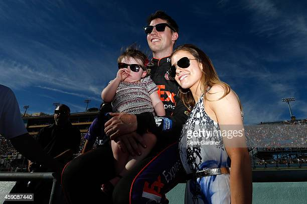 Denny Hamlin driver of the FedEx Express Toyota stands on the grid with his girlfriend Jordan Fish and his daughter Taylor James Hamlin during...