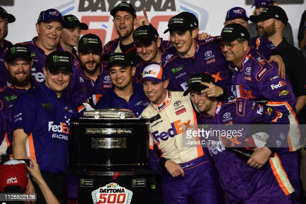 Denny Hamlin driver of the FedEx Express Toyota takes a photo with his crew members in Victory Lane after winning the Monster Energy NASCAR Cup...