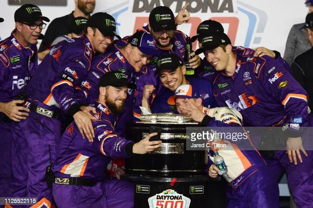 Denny Hamlin driver of the FedEx Express Toyota takes a selfie with his crew memebrs in Victory Lane after winning the Monster Energy NASCAR Cup...