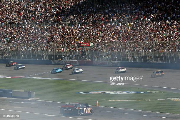Denny Hamlin driver of the FedEx Express Toyotacomes to rest on pit road after a collision with Joey Logano driver of the AAA Southern California...