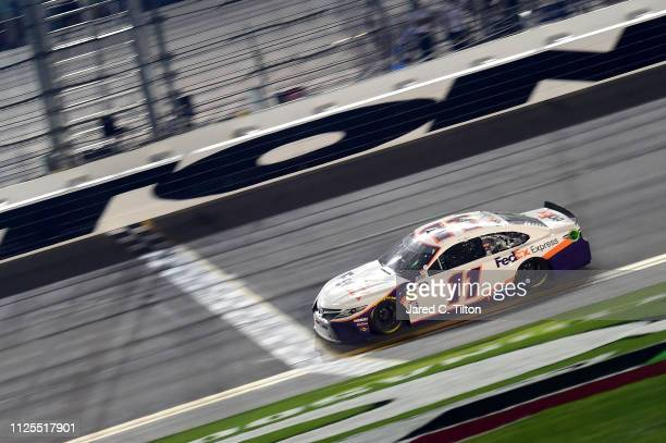 Denny Hamlin driver of the FedEx Expressc Toyota crosses the finish line to win the Monster Energy NASCAR Cup Series 61st Annual Daytona 500 at...