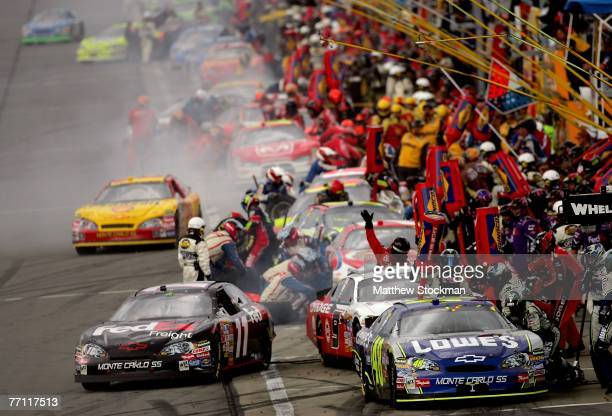 Denny Hamlin, driver of the FedEx Freight Chevrolet, pulls out of pit road past Jimmie Johnson, driver of the Lowe's Chevrolet, during the NASCAR...