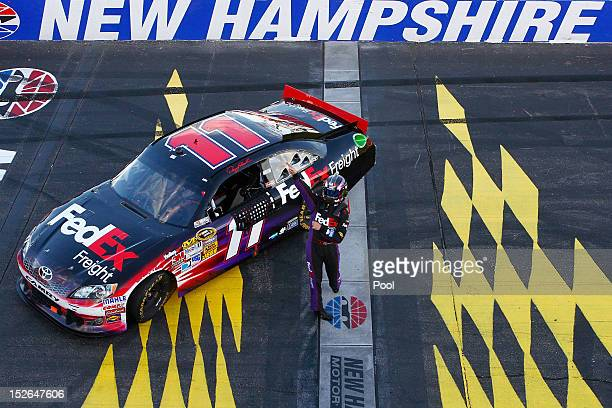 Denny Hamlin driver of the FedEx Freight Toyota celebrates after winning the NASCAR Sprint Cup Series SYLVANIA 300 at New Hampshire Motor Speedway on...
