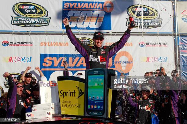 Denny Hamlin driver of the FedEx Freight Toyota celebrates in Victory Lane after winning the NASCAR Sprint Cup Series SYLVANIA 300 at New Hampshire...