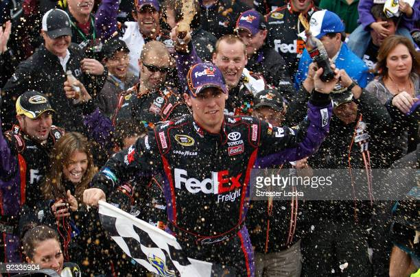 Denny Hamlin driver of the FedEx Freight Toyota celebrates in victory lane after winning the NASCAR Sprint Cup Series TUMS Fast Relief 500 at...