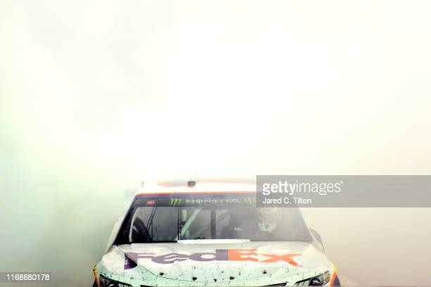 Denny Hamlin driver of the FedEx Freight Toyota celebrates with a burnout after winning the Monster Energy NASCAR Cup Series Bass Pro Shops NRA Night...