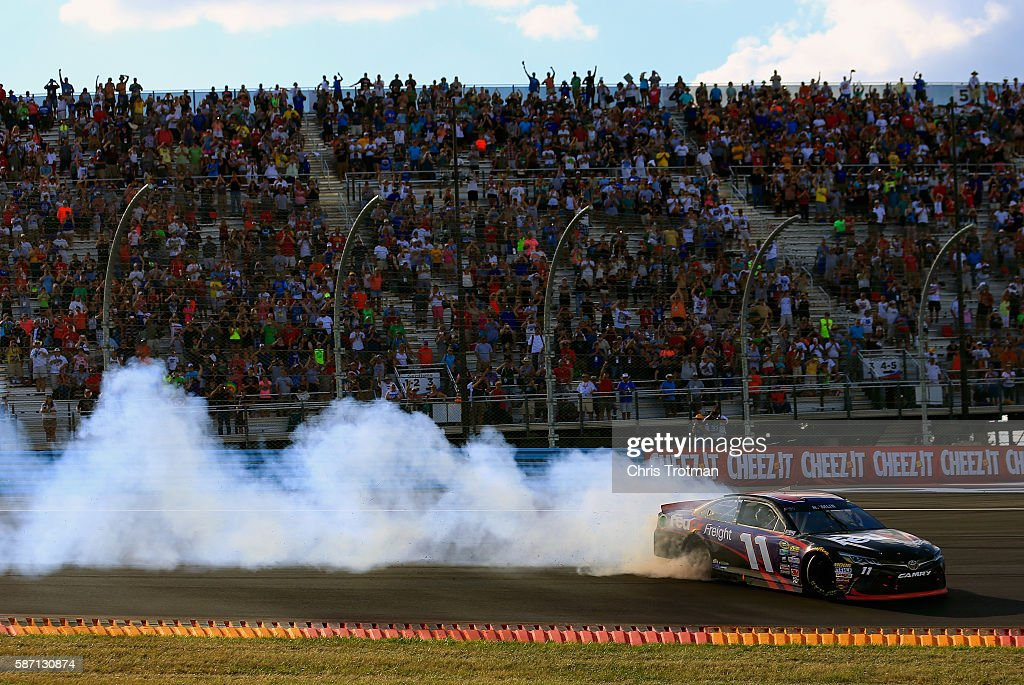 Denny Hamlin, driver of the #11 FedEx Freight Toyota, celebrates with a burnout after winning the NASCAR Sprint Cup Series Cheez-It 355 at Watkins Glen International on August 7, 2016 in Watkins Glen, New York.