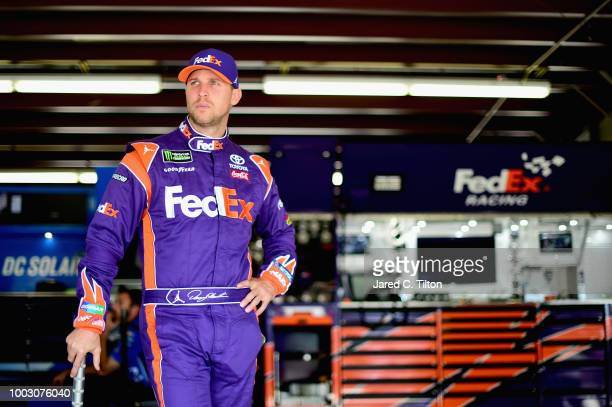 Denny Hamlin driver of the FedEx Freight Toyota stands in the garage area during practice for the Monster Energy NASCAR Cup Series Foxwoods Resort...