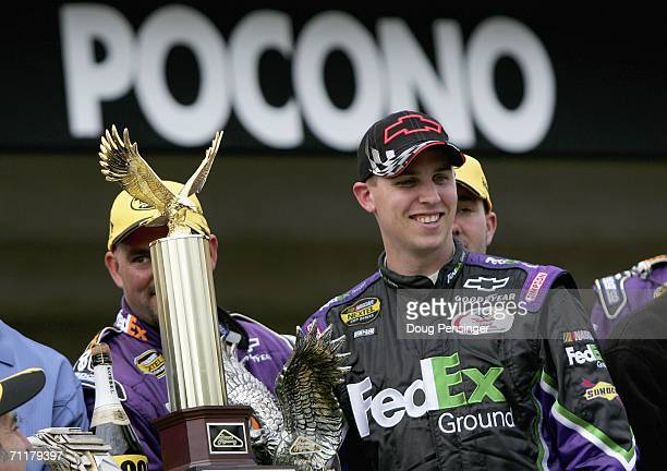 Denny Hamlin driver of the FedEx Ground Chevrolet poses with the trophy after winning the NASCAR Nextel Cup Series Pocono 500 at the Pocono Raceway...