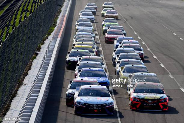 Denny Hamlin driver of the FedEx Ground Toyota and Martin Truex Jr driver of the Bass Pro Shops/Tracker Off Road Toyota lead the field during a...