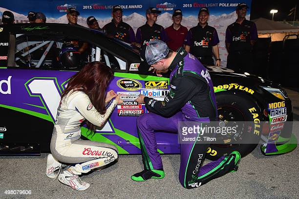 Denny Hamlin driver of the FedEx Ground Toyota and Miss Coors Light Amanda Mertz affix the Coors Light Pole award decal after Hamlin qualified for...