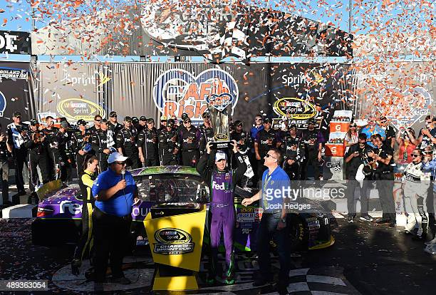 Denny Hamlin driver of the FedEx Ground Toyota celebrates in Victory Lane after winning the NASCAR Sprint Cup Series myAFibRiskcom 400 at Chicagoland...
