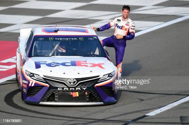 Denny Hamlin driver of the FedEx Ground Toyota celebrates winning the Monster Energy NASCAR Cup Series Gander RV 400 at Pocono Raceway on July 28...