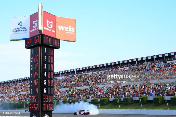 Denny Hamlin driver of the FedEx Ground Toyota celebrates with a burnout after winning the Monster Energy NASCAR Cup Series Gander RV 400 at Pocono...
