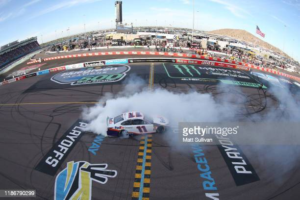 Denny Hamlin, driver of the FedEx Ground Toyota, celebrates with a burnout after winning the Monster Energy NASCAR Cup Series Bluegreen Vacations 500...