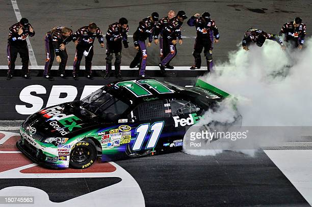 Denny Hamlin driver of the FedEx Ground Toyota celebrates with a burnout after winning the NASCAR Sprint Cup Series IRWIN Tools Night Race at Bristol...