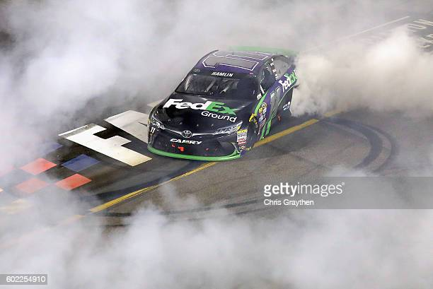 Denny Hamlin driver of the FedEx Ground Toyota celebrates with a burnout after winning the NASCAR Sprint Cup Series Federated Auto Parts 400 at...