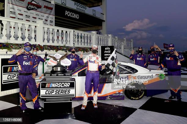 Denny Hamlin, driver of the FedEx Ground Toyota, celebrates with his teammates in victory lane after winning the NASCAR Cup Series Pocono 350 at...