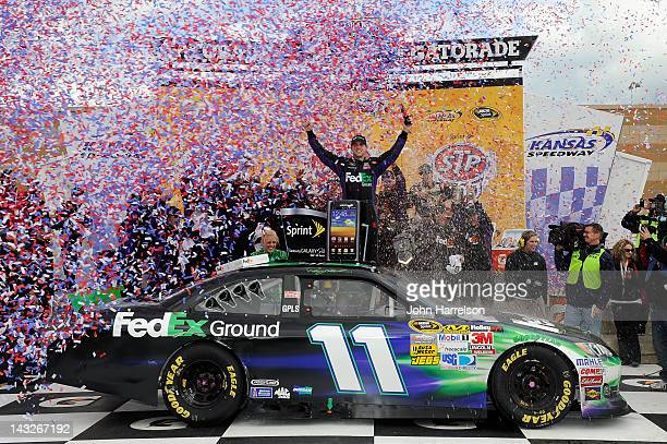 Denny Hamlin driver of the FedEx Ground Toyota celebrates with his crew in victory lane after he won the NASCAR Sprint Cup Series STP 400 at Kansas...