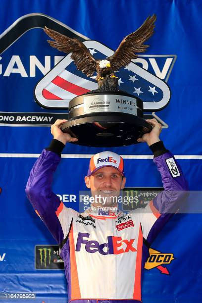 Denny Hamlin driver of the FedEx Ground Toyota celebrates with the trophy following his victory in the Monster Energy NASCAR Cup Series Gander RV 400...