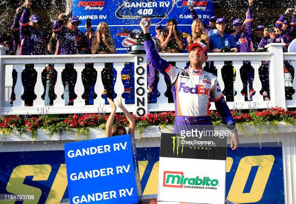 Denny Hamlin driver of the FedEx Ground Toyota clebrates in victory lane after winning the Monster Energy NASCAR Cup Series Gander RV 400 at Pocono...