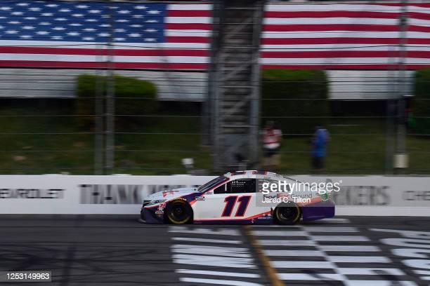 Denny Hamlin, driver of the FedEx Ground Toyota, crosses the finish line to win the NASCAR Cup Series Pocono 350 at Pocono Raceway on June 28, 2020...