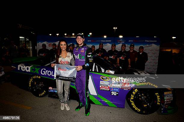 Denny Hamlin driver of the FedEx Ground Toyota poses with Miss Coors Light Amanda Mertz and the Coors Light Pole award after qualifying for pole...