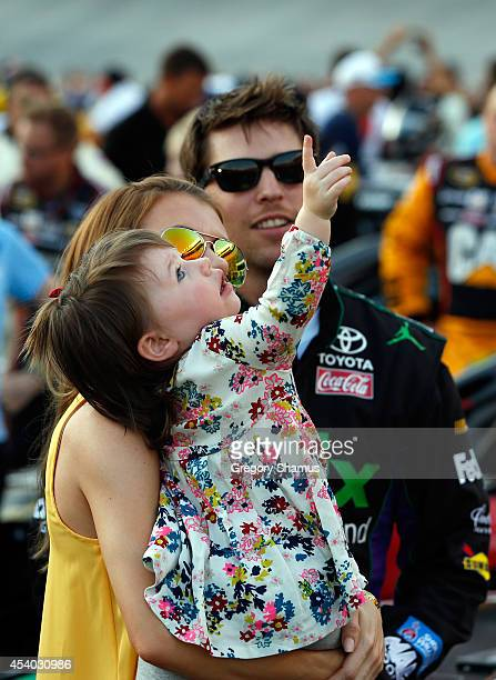 Denny Hamlin driver of the FedEx Ground Toyota stands on the grid with his girlfriend Jordan Fish and their daughter Taylor James Hamlin during...