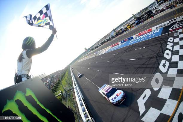Denny Hamlin driver of the FedEx Ground Toyota takes the checkered flag to win the Monster Energy NASCAR Cup Series Gander RV 400 at Pocono Raceway...