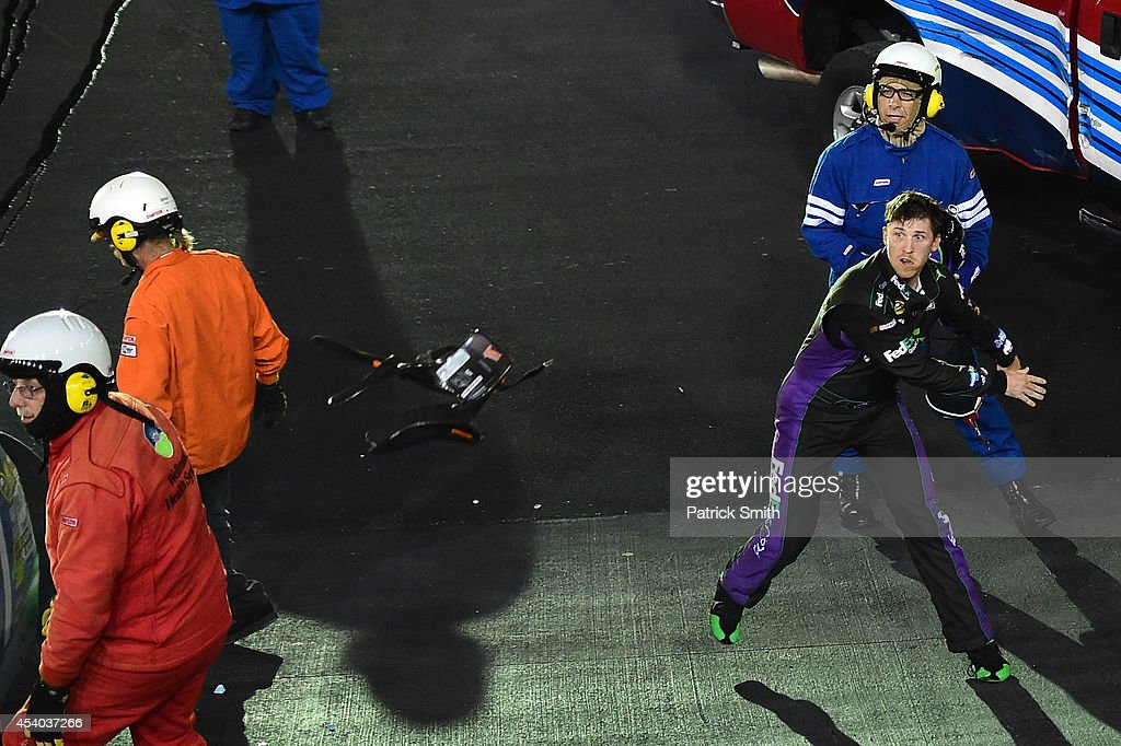Denny Hamlin, driver of the #11 FedEx Ground Toyota, throws his hans device at Kevin Harvick (not pictured), driver of the #4 Jimmy John's Chevrolet, after an on-track incident during the NASCAR Sprint Cup Series Irwin Tools Night Race at Bristol Motor Speedway on August 23, 2014 in Bristol, Tennessee.