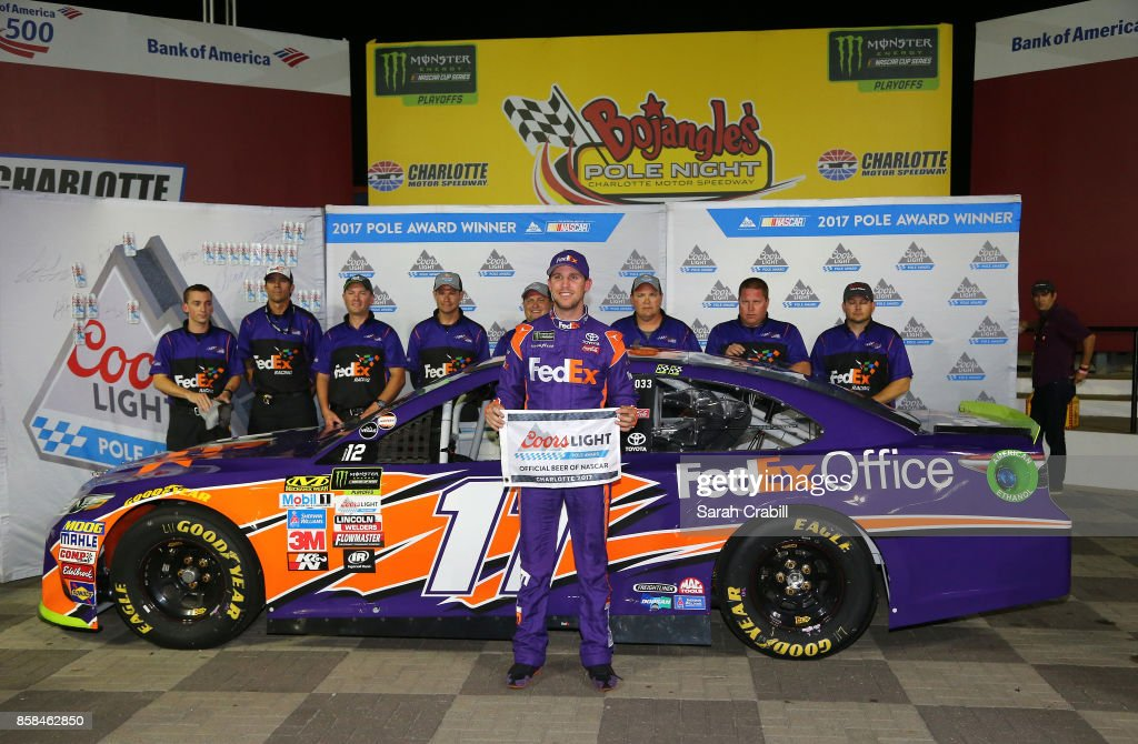 Denny Hamlin, driver of the #11 FedEx Office Toyota, and his team pose with the Coors Light Pole Award after qualifying in the pole position for the Monster Energy NASCAR Cup Series Bank of America 500 at Charlotte Motor Speedway on October 6, 2017 in Charlotte, North Carolina.