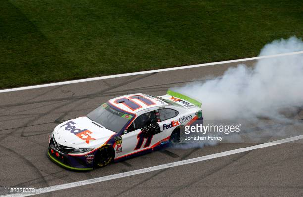 Denny Hamlin, driver of the FedEx Office Toyota, celebrates his victory with a burnout after the Monster Energy NASCAR Cup Series Hollywood Casino...
