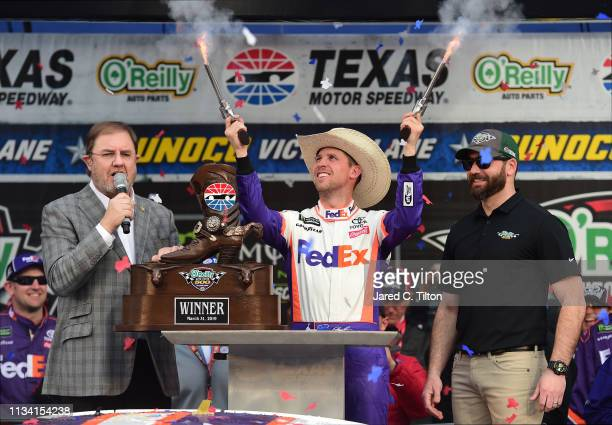 Denny Hamlin, driver of the FedEx Office Toyota, celebrates in Victory Lane after winning the Monster Energy NASCAR Cup Series O'Reilly Auto Parts...