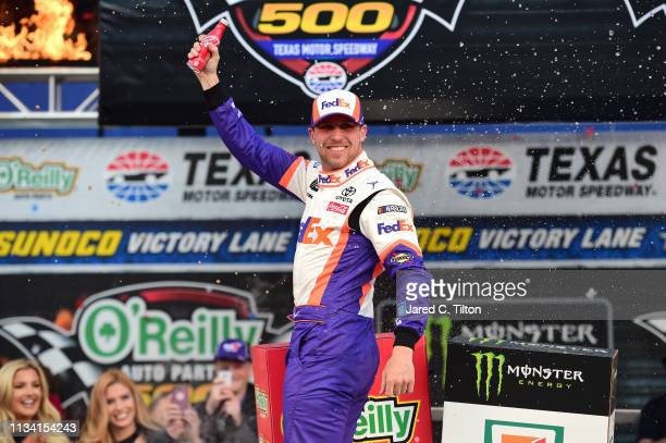 Denny Hamlin driver of the FedEx Office Toyota celebrates in Victory Lane after winning the Monster Energy NASCAR Cup Series O'Reilly Auto Parts 500...
