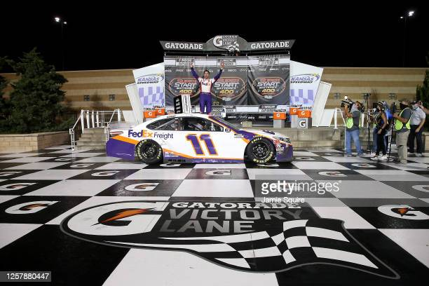 Denny Hamlin, driver of the FedEx Office Toyota, celebrates in Victory Lane after winning the NASCAR Cup Series Super Start Batteries 400 Presented...