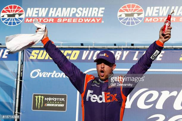 Denny Hamlin driver of the FedEx Office Toyota celebrates in Victory Lane after winning the Monster Energy NASCAR Cup Series Overton's 301 at New...