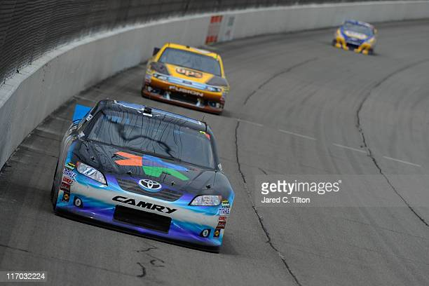 Denny Hamlin driver of the FedEx Office Toyota leads David Ragan driver of the UPS Ford during the NASCAR Sprint Cup Series Heluva Good Sour Cream...