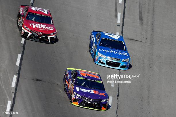 Denny Hamlin driver of the FedEx Office Toyota leads Kyle Larson driver of the Credit One Bank Chevrolet and Corey LaJoie driver of the Dr Pepper...