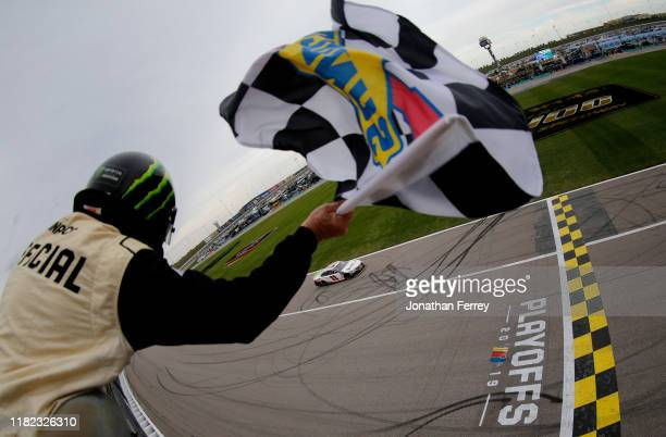Denny Hamlin, driver of the FedEx Office Toyota, takes the checkered flag to win the Monster Energy NASCAR Cup Series Hollywood Casino 400 at Kansas...
