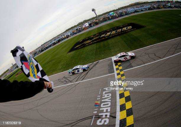 Denny Hamlin, driver of the FedEx Office Toyota, takes the checkered flag ahead of Chase Elliott, driver of the NAPA Auto Parts Chevrolet, to win the...