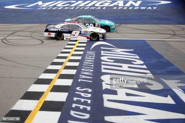 Denny Hamlin driver of the Hisense Toyota passes William Byron driver of the Liberty University Chevrolet on the last lap to win the NASCAR XFINITY...