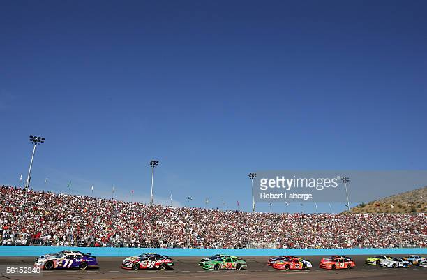 Denny Hamlin driver of the Joe Gibbs Racing FedEx Express Chevrolet leads the field at the start of the NASCAR Nextel Cup Series Checker Auto Parts...