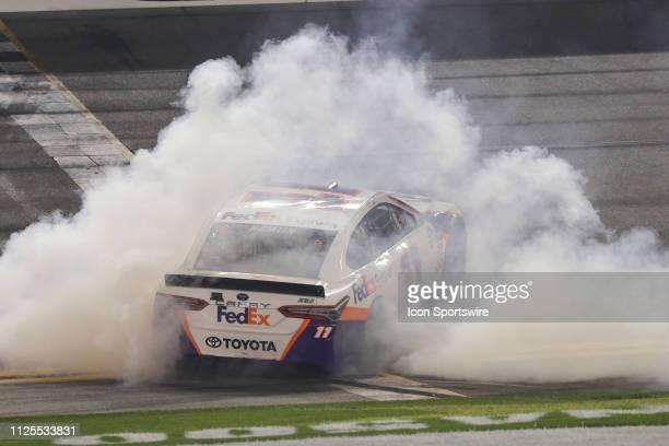 Denny Hamlin driver of the Joe Gibbs Racing FedEx Express Toyota Camry celebrates a win in the Daytona 500 on February 17 2019 at Daytona...