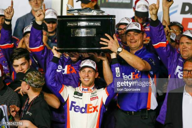Denny Hamlin driver of the Joe Gibbs Racing FedEx Express Toyota Camry lifts the Harley J Earl Trophy following the Daytona 500 on February 17 2019...