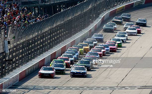 Denny Hamlin driver of the Sport Clips Toyota and Kevin Harvick driver of the Armour Sandwich Creations Chevrolet lead the field to a restart during...